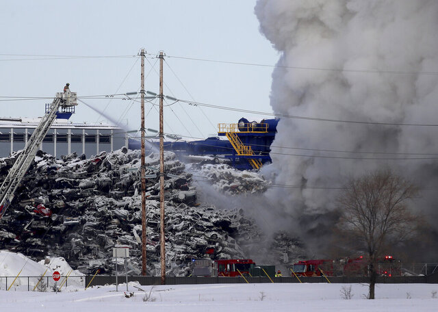 Firefighters remained on the scene of a fire that has been burning for more than 24 hours at the Northern Metal Recycling plant, Wednesday, Feb. 19, 2020, in Becker, Minn. Firefighter Toni Knutson says the fire is burning under a huge pile of cars. She says cranes are being used to remove the vehicles from the pile one-by-one. (David Joles/Star Tribune via AP)