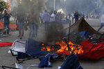 FILE - In this Oct. 29, 2019 file photo, supporters of the Shiite Hezbollah group burn tents in the camp set up by anti-government protesters near the government palace, in Beirut, Lebanon. Lebanon's protests have shown unusual overt anger at the country's powerhouse, Hezbollah. (AP Photo/Bilal Hussein, File)