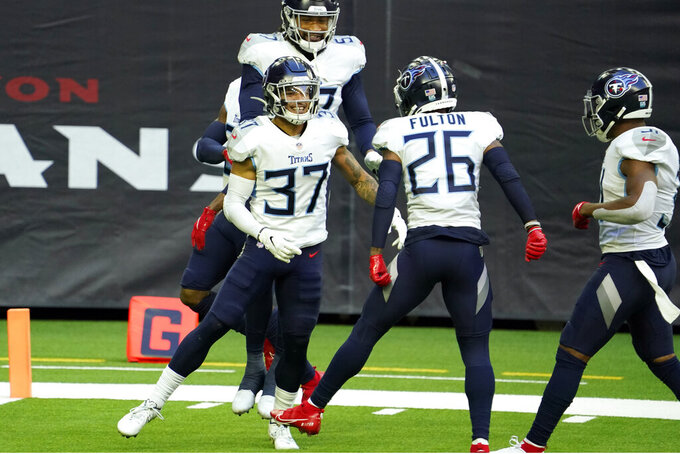 Tennessee Titans' Amani Hooker (37) celebrates with teammates after intercepting a pass during the first half of an NFL football game against the Houston Texans Sunday, Jan. 3, 2021, in Houston. (AP Photo/Sam Craft)