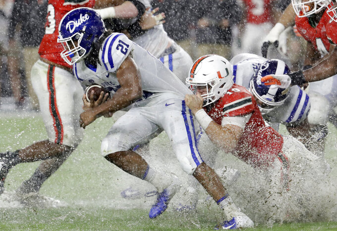 Miami defensive lineman Scott Patchan (19) attempts to tackle Duke running back Mataeo Durant (21) during the first half of an NCAA college football game Saturday, Nov. 3, 2018, in Miami Gardens, Fla. (AP Photo/Lynne Sladky)
