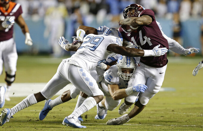Virginia Tech's Damon Hazelton (14) is tackled by North Carolina's J.K. Britt (29) and Cole Holcomb (36) during the first half of an NCAA college football game in Chapel Hill, N.C., Saturday, Oct. 13, 2018. (AP Photo/Gerry Broome)