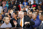 Former Malaysian Prime Minister Najib Razak, center, gets into his car outside Kuala Lumpur High Court in Kuala Lumpur, Monday, Nov. 11, 2019. A Malaysian judge on Monday ordered Najib to enter a defense at his first corruption trial linked to the multibillion-dollar looting at the 1MDB state investment fund that helped spur his shocking election ouster last year. (AP Photo/Vincent Thian)