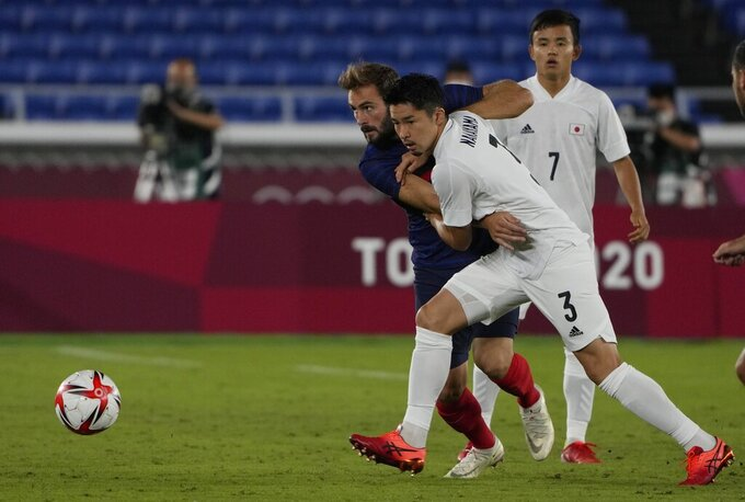 Japan's Yuta Nakayama, right, and France's Lucas Tousart, fight for the ball during a men's soccer match at the 2020 Summer Olympics, Wednesday, July 28, 2021, in Yokohama. (AP Photo/Kiichiro Sato)