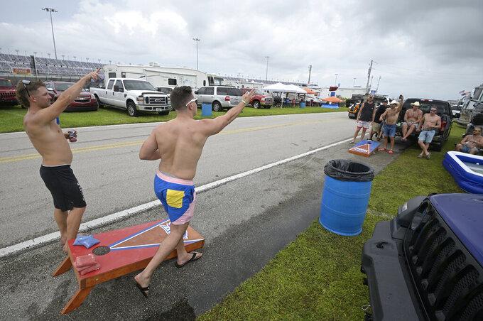 Fans play a game of corn hole before a NASCAR Xfinity Series auto race in the infield of Daytona International Speedway, Friday, Aug. 27, 2021, in Daytona Beach, Fla. (AP Photo/Phelan M. Ebenhack)