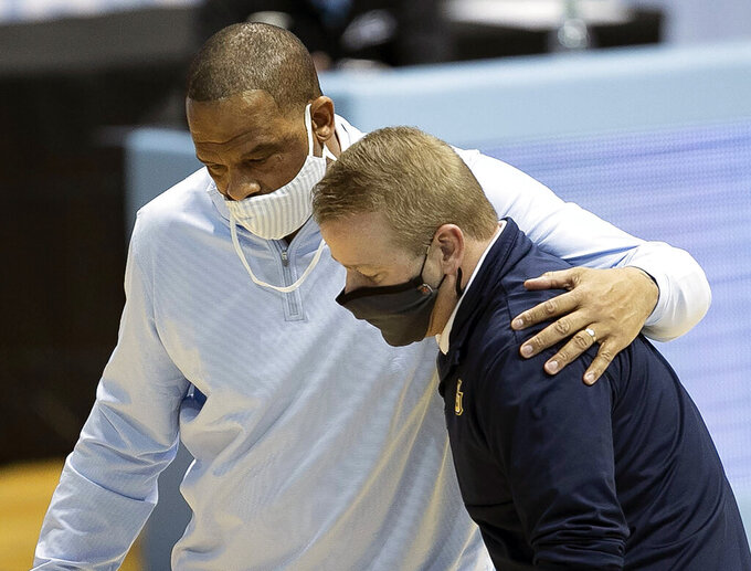 FILE - In this Feb. 24, 2021, file photo, North Carolina assistant coach Hubert Davis, left, embraces Marquette coach Steve Wojciechowski following the Marquette's win in an NCAA college basketball game in Chapel Hill, N.C. North Carolina has reached an agreement with assistant coach Hubert Davis to take over the storied men's basketball program. (Robert Willett/The News & Observer via AP, File)