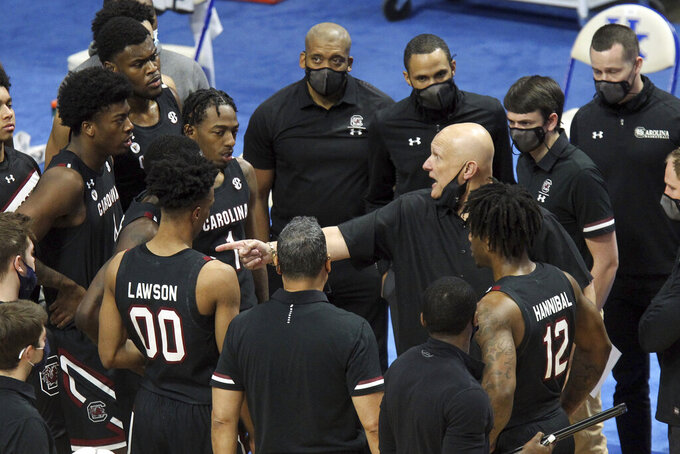 South Carolina head coach Frank Martin, center right, instructs his team during a timeout in the first half of an NCAA college basketball game against Kentucky in Lexington, Ky., Saturday, March 6, 2021. (AP Photo/James Crisp)