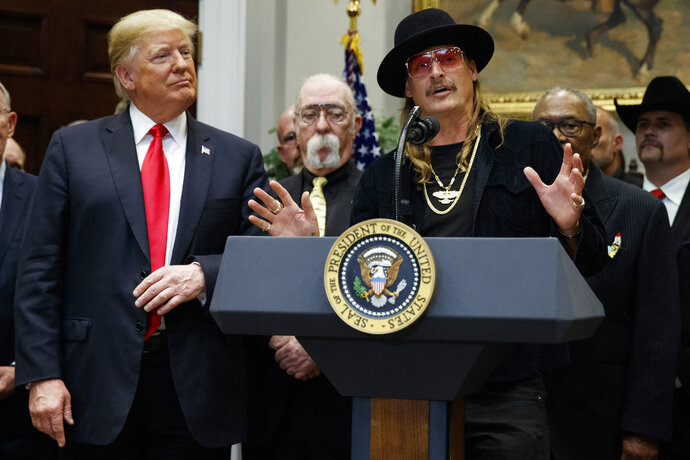 President Donald Trump looks on as musician Kid Rock speaks during a signing ceremony for the