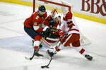 Detroit Red Wings' Luke Glendening, right, moves the puck as Florida Panthers' Josh Brown (2) and goalkeeper Chris Driedger defend during the first period of an NHL hockey game, Saturday, Dec. 28, 2019, in Sunrise, Fla. (AP Photo/Luis M. Alvarez)