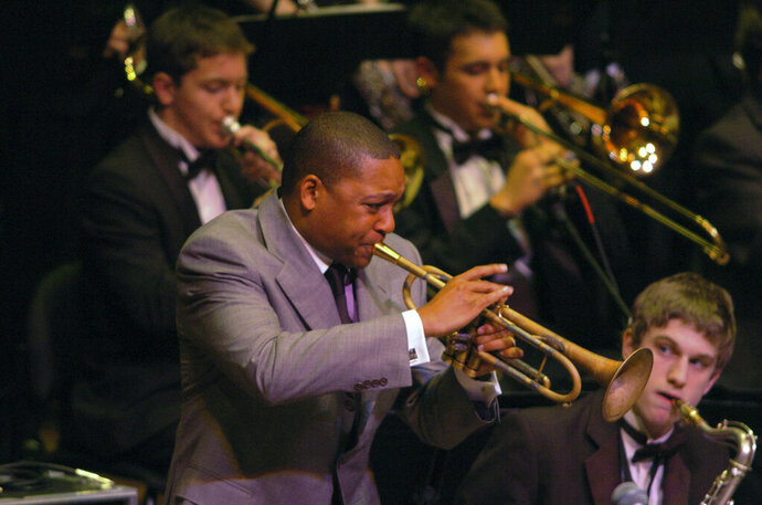 CORRECTS THE SCHOOL BAND NAME TO ROOSEVELT HIGH SCHOOL - FILE - This May 15, 2005 file photo shows Jazz great Wynton Marsalis performing with the Roosevelt High School in Seattle during the 10th Annual Essentially Ellington High School Jazz Band Competition and Festival in New York. The coronavirus pandemic has altered the annual competition and festival but it will still go on. The event will take place from June 8-12 on Jazz at Lincoln Center's website, social media accounts and also through Zoom. This year marks the 25th anniversary of the program. (AP Photo/Gina Gayle, File)