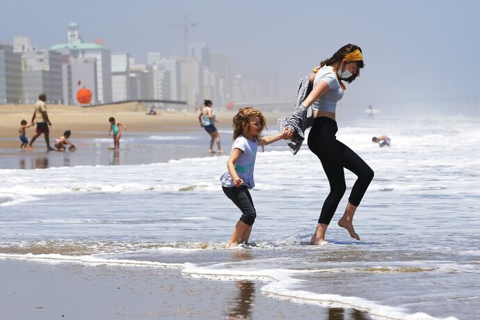 FILE - In this May 22, 2020, file photo, Victoria Faughnan, right, and Evelyn Faughnan, play in the surf in Virginia Beach, Va., the day the state reopened the beachfront during the coronavirus pandemic. The pandemic not only upended the tourism industry, but how states, cities and attractions market themselves as summer travel destinations. (AP Photo/Steve Helber, File)
