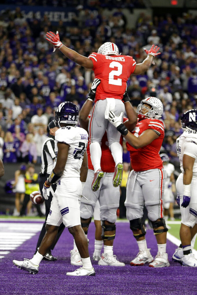 Ohio State's J.K. Dobbins (2) celebrates a touchdown run as Northwestern cornerback Montre Hartage (24) watches during the first half of the Big Ten championship NCAA college football game, Saturday, Dec. 1, 2018, in Indianapolis. (AP Photo/AJ Mast)