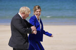 """FILE - In this file photo dated Saturday, June 12, 2021, British Prime Minister Boris Johnson and his wife Carrie walk on the boardwalk as they prepare to greet guests during the G7 meeting in St. Ives, England.  In a post on Instagram, Carrie Johnson has said she feels """"incredibly blessed to be pregnant again"""", expecting the couple's second child. (AP Photo/Kirsty Wigglesworth, FILE)"""