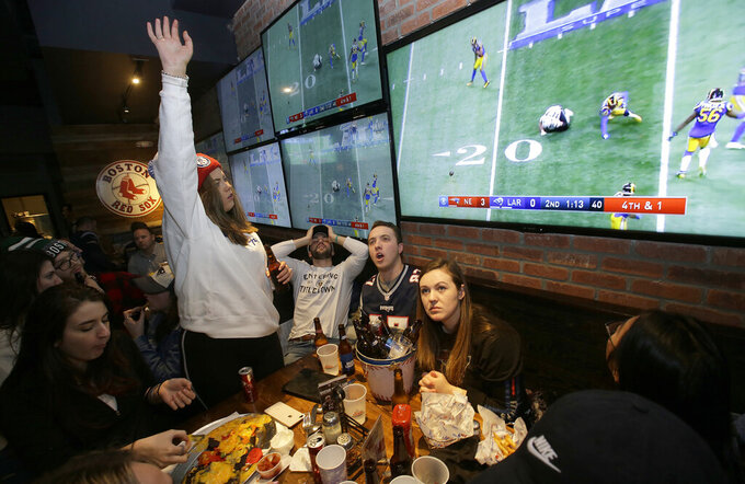 New England Patriots fans react while watching the first half of the NFL Super Bowl 53 football game in Atlanta between the Patriots and the Los Angeles Rams at a bar in Boston, Sunday, Feb. 3, 2019. (AP Photo/Steven Senne)