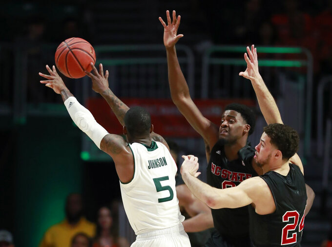 Miami guard Zach Johnson (5) passes past North Carolina State guard Devon Daniels (24) and forward DJ Funderburk, center, during the second half of an NCAA college basketball game, Thursday, Jan. 3, 2019, in Coral Gables, Fla. North Carolina State defeated Miami 87-82. (AP Photo/Wilfredo Lee)