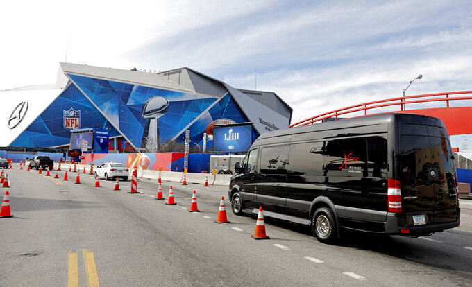 A limousine van drives by Mercedes-Benz Stadium ahead of Sunday's NFL Super Bowl 53 football game between the Los Angeles Rams and New England Patriots in Atlanta, Friday, Feb. 1, 2019. Limousine companies are 300 to 400 vehicles short of what's needed to transport NFL owners, corporate clients and Very Important People this weekend, an executive with Atlanta's Super Bowl Host committee has been told by transportation firms. (AP Photo/David Goldman)