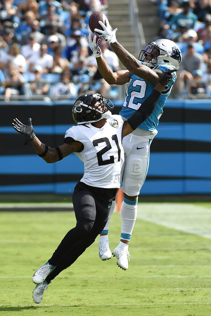 Carolina Panthers wide receiver D.J. Moore (12) catches a pass while Jacksonville Jaguars cornerback A.J. Bouye (21) defends during the first half of an NFL football game in Charlotte, N.C., Sunday, Oct. 6, 2019. (AP Photo/Mike McCarn)
