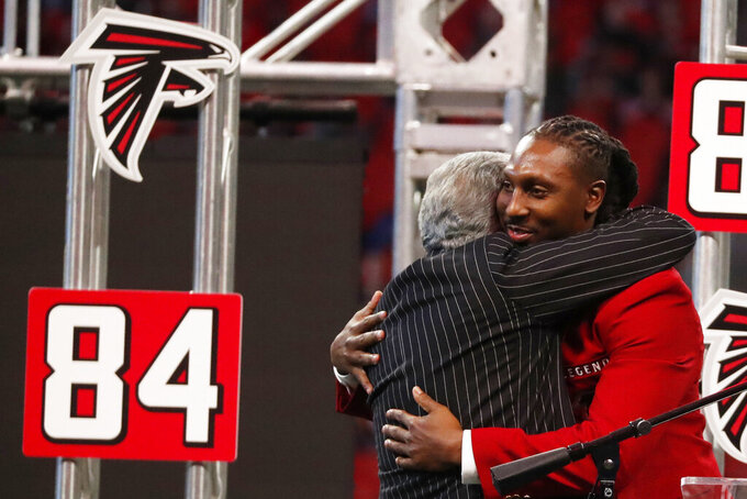 Former Atlanta Falcons player Roddy White is embraced by Atlanta Falcons Owner Arthur Blank during half time of an NFL football game between the Atlanta Falcons and the Carolina Panthers, Sunday, Dec. 8, 2019, in Atlanta. (AP Photo/John Bazemore)