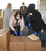 In a photo provided by Project Isaiah, volunteers assisting the Project Isaiah food-relief effort transfer boxes of items in an area outside St. Christopher's Hospital for Children in Philadelphia on April 24, 2020. The prepackaged meals later were distributed to thousands of families in the city. (Rudolph Lauletta Jr./Project Isaiah via AP)