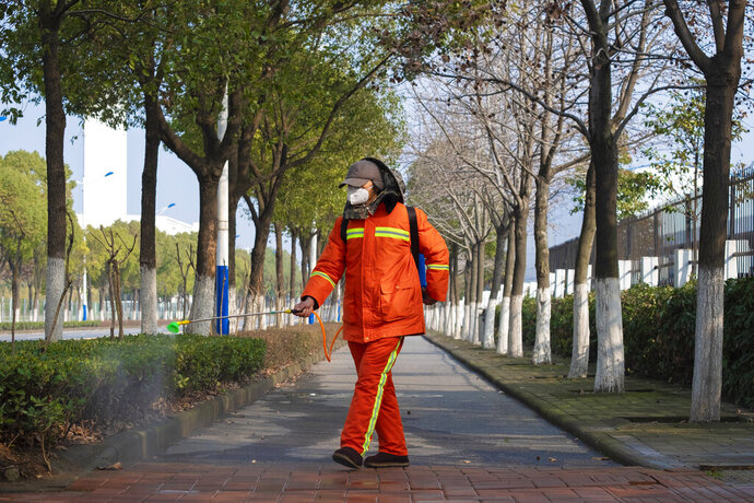 A worker wearing a face mask sprays disinfectant along a path in Wuhan in central China's Hubei Province, Tuesday, Jan. 28, 2020. China's death toll from a new viral disease that is causing global concern rose by 25 to at least 106 on Tuesday as the United States and other governments prepared to fly their citizens out of the locked-down city at center of the outbreak. (AP Photo/Arek Rataj)