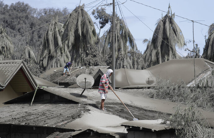 Residents clear their roofs covered with volcanic ash at Laurel, Batangas province, southern Philippines on Tuesday, Jan. 14, 2020. Taal volcano is spewing ash half a mile high and trembling with earthquakes constantly as thousands of people flee villages darkened and blanketed by heavy ash. (AP Photo/Aaron Favila)