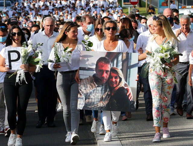 This July 8, 2020 file photo shows Veronique Monguillot, wife of Philippe Monguillot, a bus driver who was attacked in Bayonne on Sunday night, holding a photo of her with her husband, during a protest march in Bayonne, southwestern France. The wife of a French bus driver savagely beaten after he asked four of his passengers to wear face masks aboard his vehicle called Saturday for
