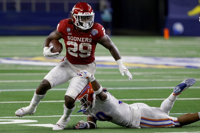 Oklahoma running back Rhamondre Stevenson (29) breaks a tackle attempt by Florida linebacker Amari Burney, right, on his way to a touchdown during the second half of the Cotton Bowl NCAA college football game in Arlington, Texas, Wednesday, Dec. 30, 2020. (AP Photo/Ron Jenkins)