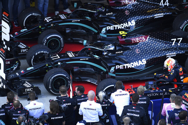 Drivers arrive in the winners circle after the Russian Formula One Grand Prix, at the Sochi Autodrom circuit, in Sochi, Russia, Sunday, Sept. 27, 2020. Drivers from left, Mercedes driver Lewis Hamilton of Britain, third place, Mercedes driver Valtteri Bottas of Finland, first place, and Red Bull driver Max Verstappen of the Netherlands, second place. (Kirill Kudryavtsev, Pool via AP)