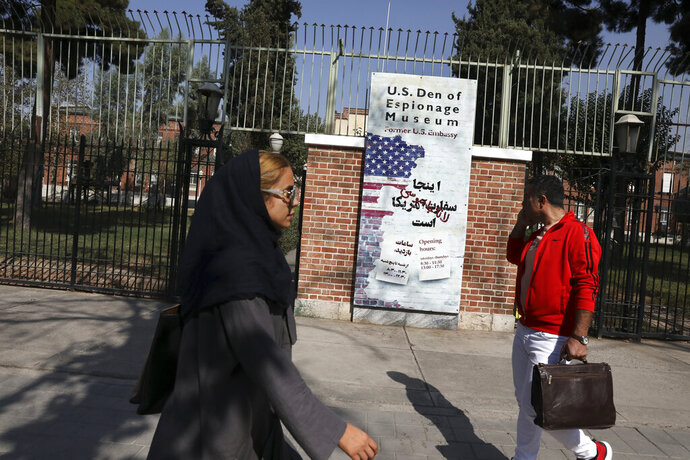 In this Tuesday, Oct. 15, 2019 photo, Iranians walk past anti-U.S. graffiti on the wall of the former U.S. Embassy, in Tehran, Iran. For those who were there, the memories are still fresh 40 years after one of the defining events of Iran's 1979 Islamic Revolution, when protesters seized the U.S. Embassy in Tehran and set off a 444-day hostage crisis whose consequences continue to reverberate to this day. (AP Photo/Vahid Salemi)