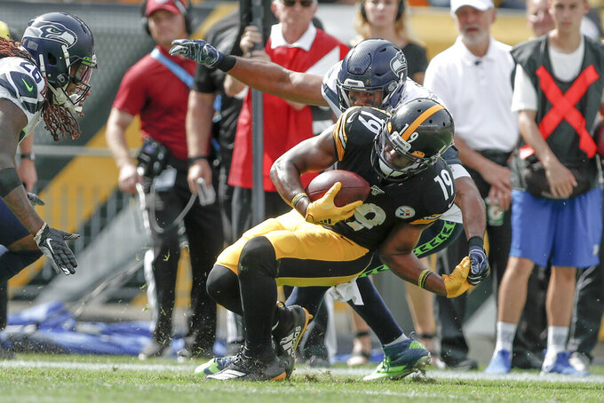 Pittsburgh Steelers wide receiver JuJu Smith-Schuster (19) tries to Geta away from Seattle Seahawks outside linebacker K.J. Wright, top, in the second half of an NFL football game Sunday, Sept. 15, 2019, in Pittsburgh. (AP Photo/Don Wright)