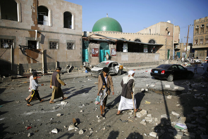 FILE - In this Sept. 3, 2015, file photo people walk at the site of a car bomb attack next to a Shiite mosque in Sanaa, Yemen. Yemen's civil war has exacted an enormous toll on people with disabilities, who find themselves on the margins of society and excluded from badly needed humanitarian assistance, Amnesty International said in a report released Tuesday, Dec. 3, 2019. (AP Photo/Hani Mohammed, File)