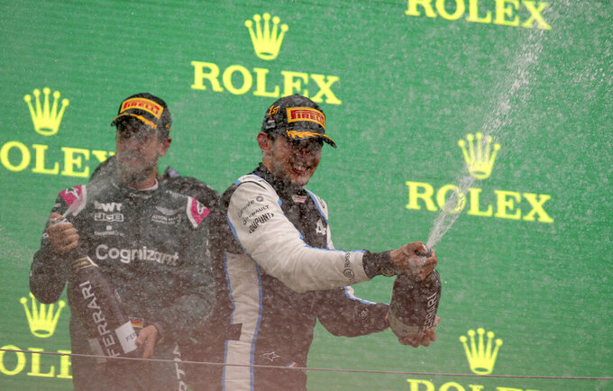 Alpine driver Esteban Ocon of France, right, celebrates on the podium after winning with second placed Aston Martin driver Sebastian Vettel of Germany after the Hungarian Formula One Grand Prix, at the Hungaroring racetrack in Mogyorod, Hungary, Sunday, Aug. 1, 2021. (Florion Goga/Pool via AP)