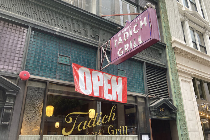 An open banner hangs outside the Tadich Grill, California's oldest restaurant, in San Francisco, on June 4, 2021. California, the first state in America to put in place a coronavirus lockdown, is now turning a page on the pandemic. Most of California's coronavirus restrictions will disappear Tuesday, June 15, 2021. (AP Photo/Eric Risberg)