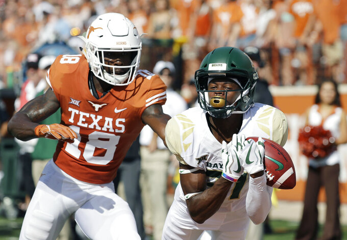 Baylor wide receiver Denzel Mims (15) makes a 19-yard catch in front of Texas defensive back Davante Davis (18) defends the play during the first half of an NCAA college football game, Saturday, Oct. 13, 2018, in Austin, Texas. (AP Photo/Eric Gay)