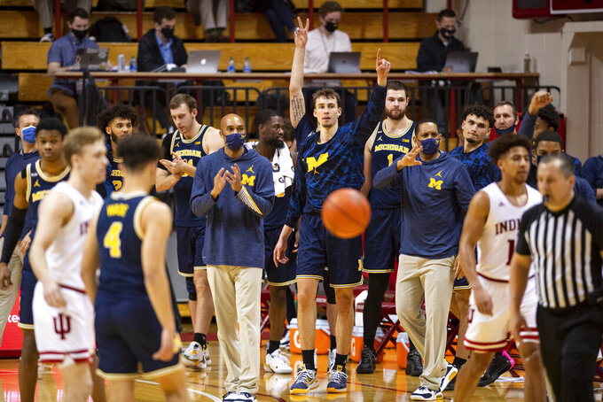 Michigan staff and players react after defeating Indiana in an NCAA college basketball game, Saturday, Feb. 27, 2021, in Bloomington, Ind.  (AP Photo/Doug McSchooler)