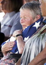 In this Thursday, Aug. 9, 2018 photo, Marjory Ideus, sister of World War II Flight Officer Richard Lane, holds the flag from Lane's casket during burial services at Filley Cemetery in Filley, Neb. The remains of the World War II pilot were finally buried with full military honors in his home state of Nebraska after 73 years in foreign soil. Lane, who died in combat in 1944, had been buried in a military cemetery in Belgium in a grave marked
