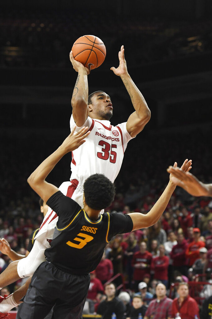Arkansas forward Reggie Chaney (35) is called for an offensive foul as he tries to drive past Missouri defender Ronnie Suggs (3) during the first half of an NCAA college basketball game, Wednesday, Jan. 23, 2019, in Fayetteville, Ark. (AP Photo/Michael Woods)