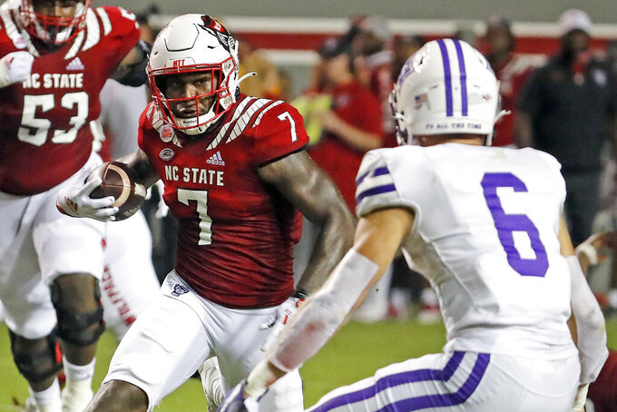 North Carolina State's Zonovan Knight (7) is challenged by Furman's Hugh Ryan (6) during the first half of an NCAA college football game in Raleigh, N.C., Saturday, Sept. 18, 2021. (AP Photo/Karl B DeBlaker)