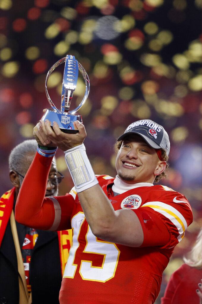 Kansas City Chiefs' Patrick Mahomes holds up the Lamar Hunt Trophy after the NFL AFC Championship football game against the Tennessee Titans Sunday, Jan. 19, 2020, in Kansas City, MO. The Chiefs won 35-24 to advance to Super Bowl 54. (AP Photo/Charlie Neibergall)
