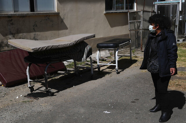 Herminia Carpio looks at the body of her brother Guillermo covered by a slim mattress outside the General Hospital before his body is taken away by a funeral home in La Paz, Bolivia, Wednesday, July 22, 2020. Carpio said her 58-year-old brother died the previous afternoon, and according to the hospital he died of COVID-19. (AP Photo/Juan Karita)