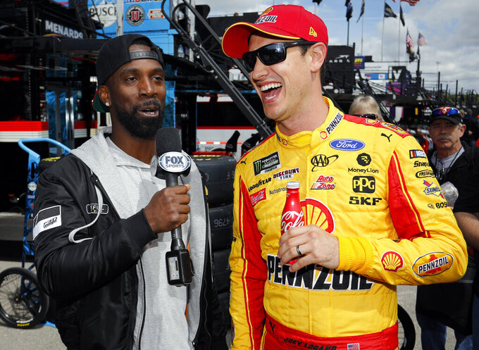 Philadelphia Phillies' Andrew McCutchen, left, interviews NASCAR Cup Series driver Joey Logano, right, at Kansas Speedway in Kansas City, Kan., Friday, May 10, 2019. McCutchen is in town to play the Kansas City Royals. (AP Photo/Colin E. Braley)