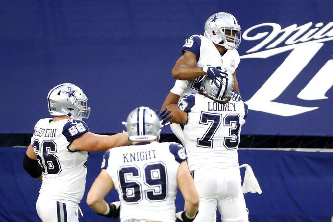 Dallas Cowboys' Connor McGovern (66), Brandon Knight (69) and Joe Looney (73) celebrate with Amari Cooper after his touchdown catch in the first half of an NFL football game against the Washington Football Team in Arlington, Texas, Thursday, Nov. 26, 2020. (AP Photo/Roger Steinman)