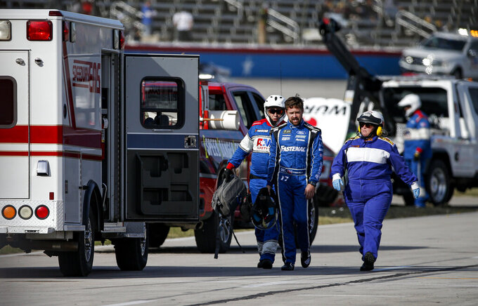 Ricky Stenhouse Jr., center, is escorted to an ambulance as a precaution after wrecking exiting his vehicle during a NASCAR auto race at Texas Motor Speedway, Sunday, Nov. 3, 2019, in Fort Worth, Texas. (AP Photo/Brandon Wade)