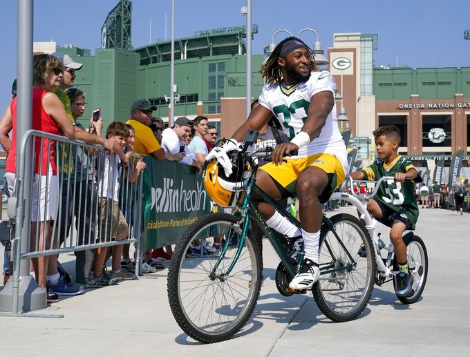 Green Bay Packers' Aaron Jones rides a bike to NFL football training camp Thursday, July 25, 2019, in Green Bay, Wis. (AP Photo/Morry Gash)