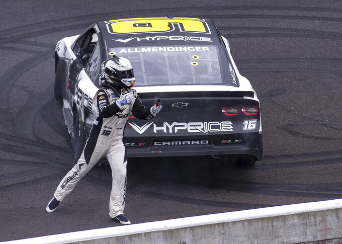 AJ Allmendinger (16) celebrates at the finish line after winning a NASCAR Cup Series auto race at Indianapolis Motor Speedway, Sunday, Aug. 15, 2021, in Indianapolis. (AP Photo/Doug McSchooler)