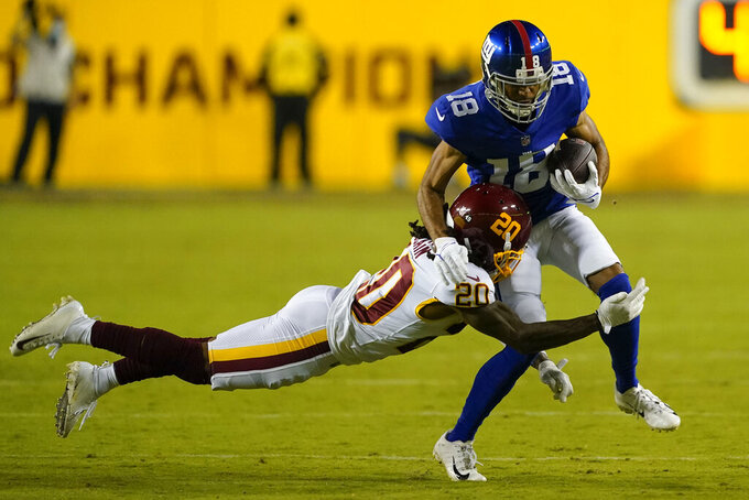 New York Giants wide receiver C.J. Board (18) is tackled by Washington Football Team cornerback Bobby McCain (20) during the first half of an NFL football game, Thursday, Sept. 16, 2021, in Landover, Md. (AP Photo/Al Drago)