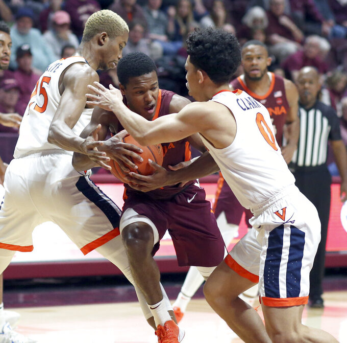 Virginia Tech's Jalen Cone (15) is defended by Virginia's Mamadi Diakite (25) and Kihei Clark (0) during the first half of an NCAA college basketball game Wednesday, Feb. 26, 2020, in Blacksburg, Va. (Matt Gentry/The Roanoke Times via AP)