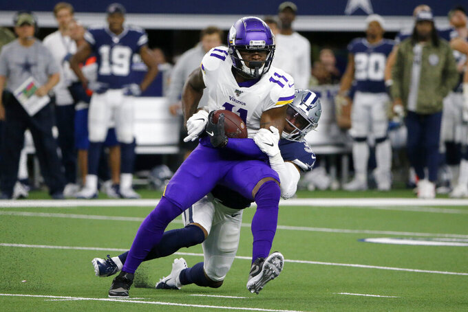 Minnesota Vikings wide receiver Laquon Treadwell (11) catches a pass as Dallas Cowboys' Xavier Woods (25) defends during the first half of an NFL football game in Arlington, Texas, Sunday, Nov. 10, 2019. (AP Photo/Michael Ainsworth)