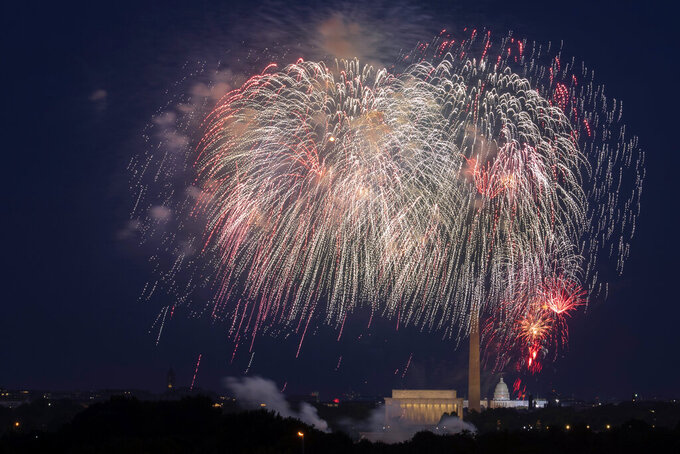 FILE - In this Saturday, July 4, 2020, file photo, Fourth of July fireworks explode over the Lincoln Memorial, the Washington Monument and the U.S. Capitol along the National Mall in Washington. President Joe Biden wants to imbue Independence Day with new meaning in 2021 by encouraging nationwide celebrations to mark the country's effective return to normalcy after 16 months of pandemic disruption. The White House says the National Mall in Washington will host the traditional fireworks ceremony and it's encouraging other communities hold festivities as well. (AP Photo/Cliff Owen, File)