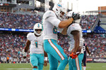 Miami Dolphins wide receiver Jaylen Waddle, right, celebrates with Mike Gesicki after his touchdown during the second half of an NFL football game against the New England Patriots, Sunday, Sept. 12, 2021, in Foxborough, Mass. At left is Miami Dolphins quarterback Tua Tagovailoa (1). (AP Photo/Winslow Townson)