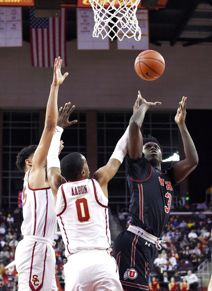 Utah forward Donnie Tillman, right, shoots as Southern California forward Bennie Boatwright, left, and guard Shaqquan Aaron defend during the first half of an NCAA college basketball game Wednesday, Feb. 6, 2019, in Los Angeles. (AP Photo/Mark J. Terrill)